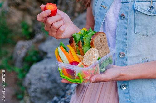 Foto op Aluminium Assortiment Young hipster girl eating plum from lunch box