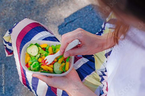 In de dag Assortiment Young woman eating from lunch box