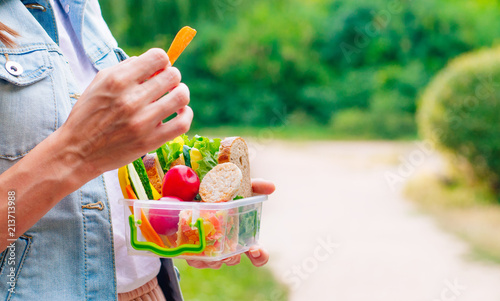 Foto op Aluminium Assortiment Young woman eating from lunch box outdoor