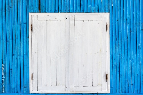 Fotografering  White wooden window with rusty door hinges on blue bamboo wall of a shack at the beach in the island of Koh Phangan, Thailand