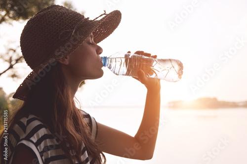 Woman drinking water in summer morning sun