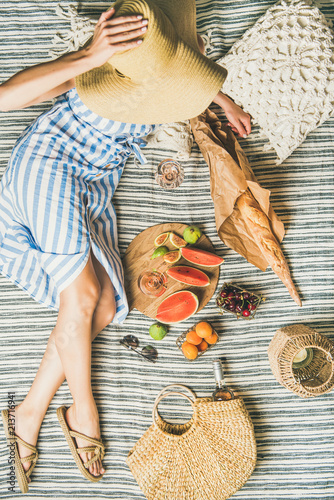 Keuken foto achterwand Summer picnic setting. Young woman in striped dress and straw sunhat sitting with rose wine, fresh fruit on board and baguette on blanket, top view. Outdoor gathering or lunch concept