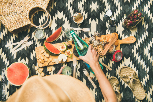 Keuken foto achterwand Summer beach picnic setting. Flat-lay of charcuterie board with snacks, watermelon, cherries, beach feminine accesories over picnic blanket, top view, copy space. Girl pouring soda from bottle