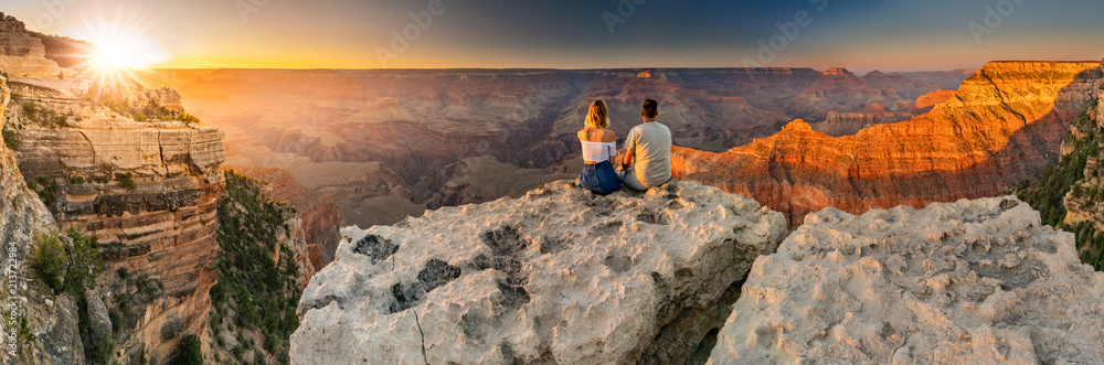 Fototapety, obrazy: A man and a woman sit at the edge of the Grand Canyon at sunset minutes