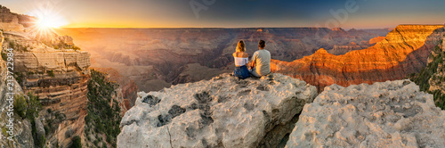 Fotografie, Tablou A man and a woman sit at the edge of the Grand Canyon at sunset minutes