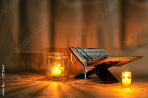 Photo  The Quran is placed on a wooden stand.Light candles.