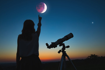 Fototapeta Girl looking at lunar eclipse through a telescope. My astronomy work.