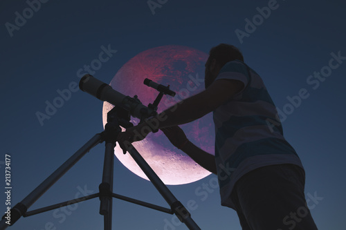 Man looking at lunar eclipse through a telescope. My astronomy work.