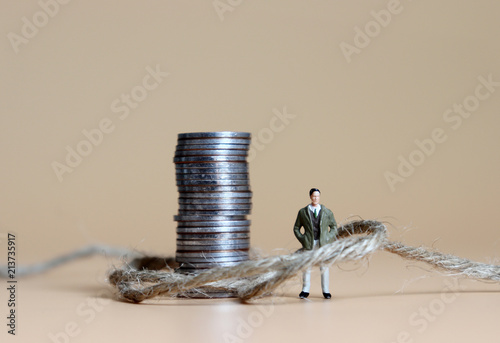Photo A miniature man connected with a pile of coins and rope.