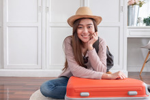 Young Asian Woman Traveler Packing Stuff In Orange Suitcase Prepare For Holiday Vacation At Home.backpacker Travel Concept.