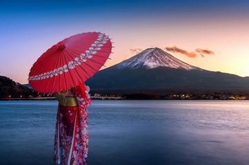 Asian woman wearing japanese traditional kimono at Fuji mountain. Sunset at Kawaguchiko lake in Japan.
