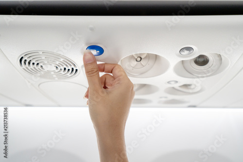 Close up of asian flight attendant's hand call cabin crew or stewardess by pressing help needed button on overhead compartment Wallpaper Mural