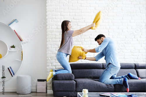 Valokuva  Portrait of Young Couple Playing Pillow Fight