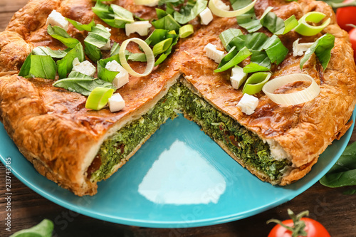 Tasty pie with spinach on table