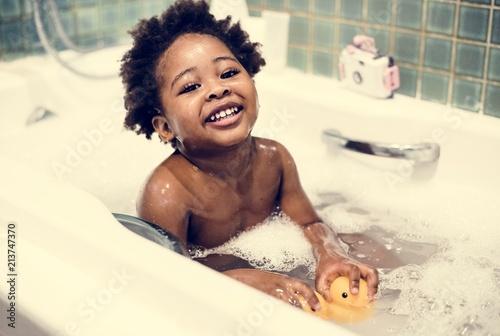 Canvas African descent kid enjoying bath tub