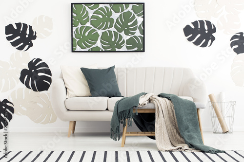 Fototapety, obrazy: Green blanket on stool in front of couch in living room interior with poster of leaves. Real photo