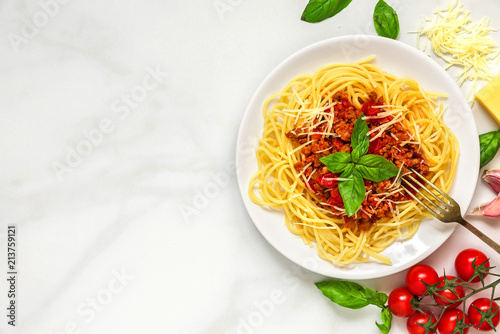 Spaghetti bolognese on a white plate with fork on white marble table. healthy food. top view