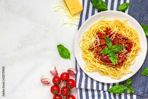 pasta spaghetti bolognese on a white plate on kitchen towel over white marble table. healthy food. top view