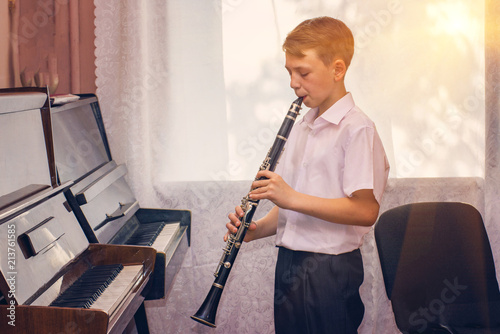 The boy plays the clarinet near the black piano by the window Fototapeta