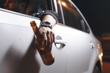 Drunk Young Man Drives A Car With A Bottle Of Beer. This Is A Campaign Picture Of Don't Drink For Drive.