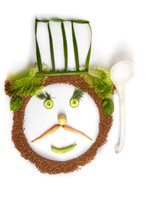 Cheerful Chef's Face Made From Vegetables, Lettuce, Kortoshka, Basil, Carrot Green Onion Cucumber, Carrots, Peas, Black Pepper And Buckwheat Photographed On A White Background Isolate