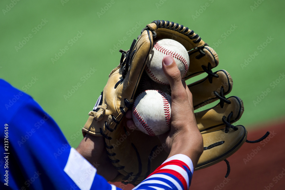 An arm stretches out to catch a baseball using a worn leather glove ...