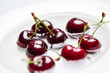 Fresh cherries in water on a white dish