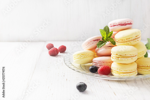 Poster Macarons Different types of macarons on white wooden table. Copyspace.