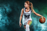 Portrait of a beautiful and sexy woman with a basketball in studio. Sport concept