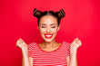 Leinwandbild Motiv Close up portrait of happy young woman with toothy smile clasp hands in fists and celebrate achievement goal isolated on red bright background