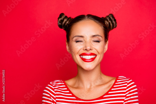 Close up the girl's face with a wide smile and blinked eyes with happiness isolated on red bright background