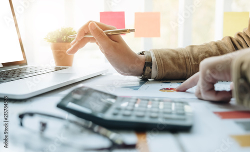 Fototapeta Close up Businessman and partner using calculator and laptop for calaulating finance, tax, accounting, statistics and analytic research concept obraz