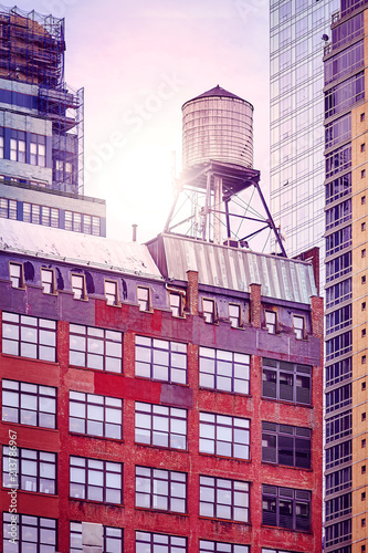 In de dag New York City Water tank on a roof at sunset, color toned picture, New York City, USA.