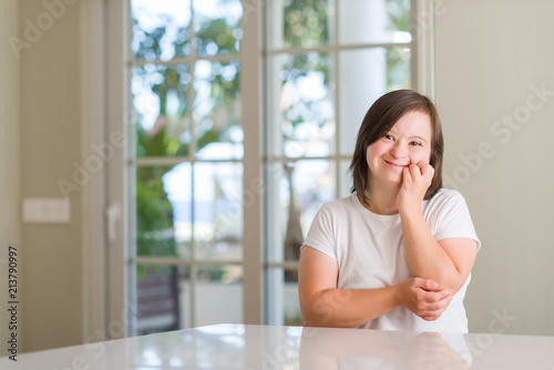 Fotografie, Obraz Down syndrome woman at home looking stressed and nervous with hands on mouth biting nails