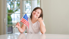 Down Syndrome Woman At Home Holding Flag Of Usa Pointing And Showing With Thumb Up To The Side With Happy Face Smiling