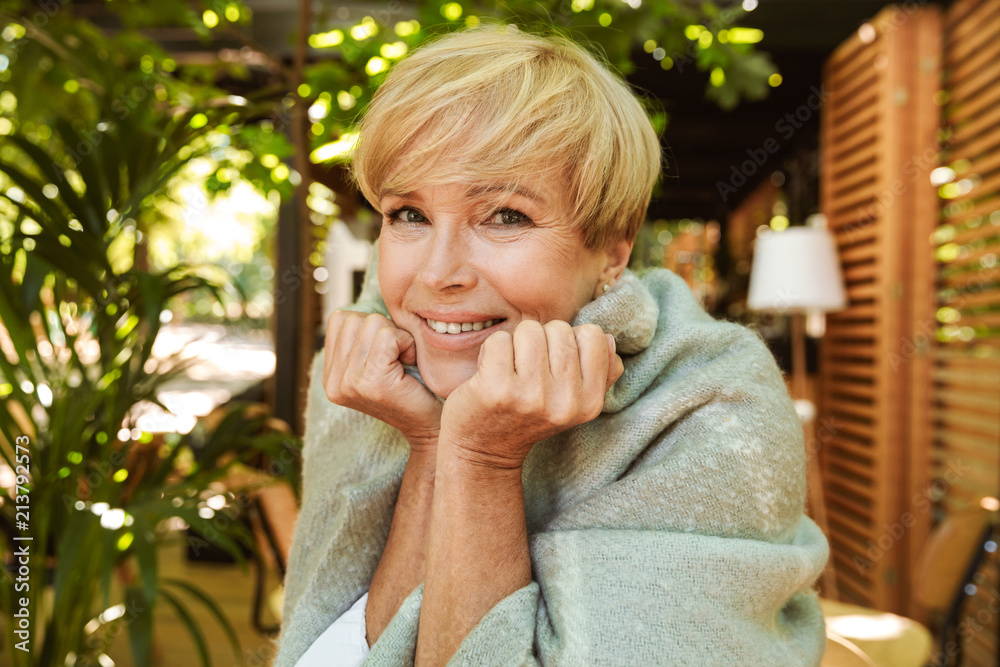Fototapeta Smiling mature woman wrapped in blanket relaxing