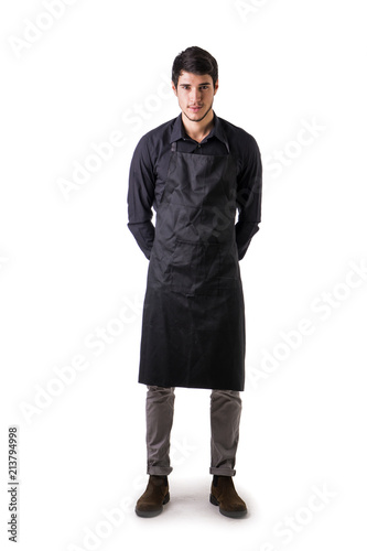 Photo Young chef or waiter posing, wearing black apron and shirt isolated on white bac