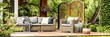 Panorama of wicker garden furniture with cozy pillows and blankets on a wooden terrace in beautiful outdoor greenery