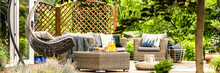 Cozy Hanging Egg Chair, Stylish Garden Furniture And Fruit On A Wicker Table On A Spacious Terrace Among Green Plants And Trees