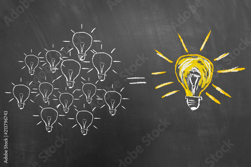 Brainstorming concept with light bulb on chalkboard or blackboard.