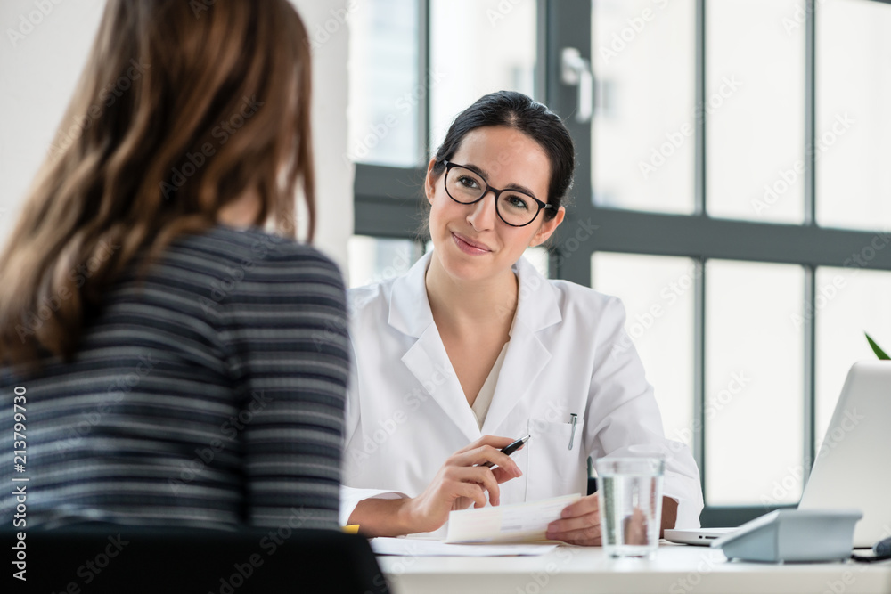 Fototapeta Female physician listening to her patient during consultation while sitting down in the office of a modern medical center