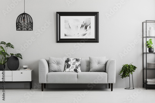 Obraz Black industrial bookcase and a plant stand next to an upholstered sofa in a gray living room interior with place for a coffee table. Real photo - fototapety do salonu