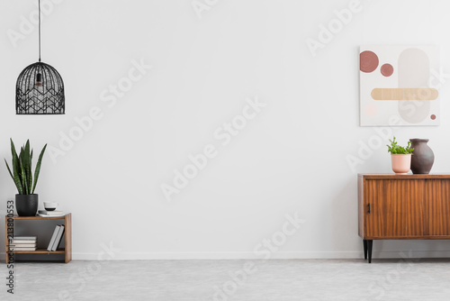 Fotografía  Retro, wooden cabinet and a painting in an empty living room interior with white walls and copy space place for a sofa