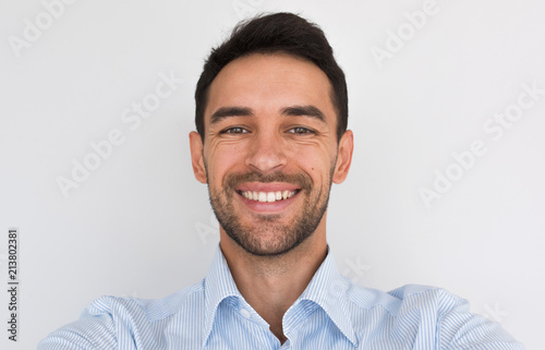 Fotografía Closeup portrait of happy handsome young male smiling with healhty toothy smile looking at the camera, making self portrait
