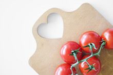 Cherry Tomatoes On A Branch Lie On A Wooden Cutting Board On A White Table. The Heart Is Cut Out On The Board.