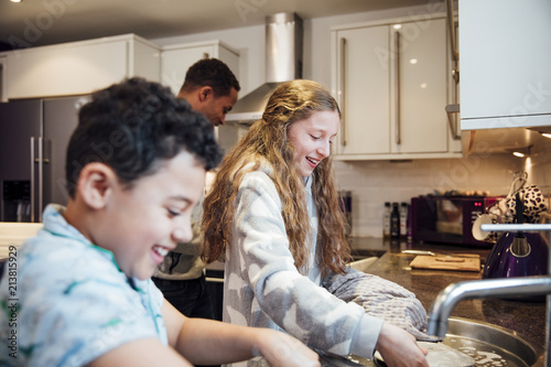 Foto  Siblings Doing the Dishes at Home
