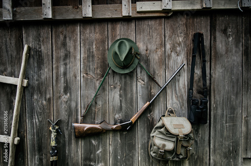 Aluminium Prints Hunting Professional hunters equipment for hunting. Rifle, hat, bag and others on a wooden black background.