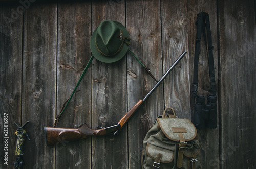 Garden Poster Hunting Professional hunters equipment for hunting. Rifle, hat, bag and others on a wooden black background.