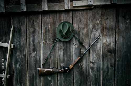 Fotobehang Jacht Professional hunters equipment for hunting. Rifle, hat, bag and others on a wooden black background.