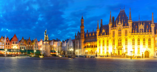 Fototapeta na wymiar Panoramic view of typical Flemish colored houses and statue of Jan Breydel and Pieter de Coninck on the Grote Markt or Market Square during evening blue hour, Bruges, Belgium